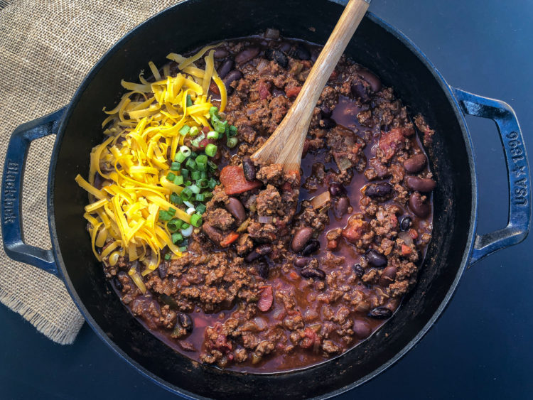 A full pot of awesome chili garnished with shredded cheddar cheese and green onions.