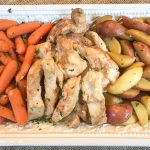 Carrots, chicken, and potatoes on a white serving platter