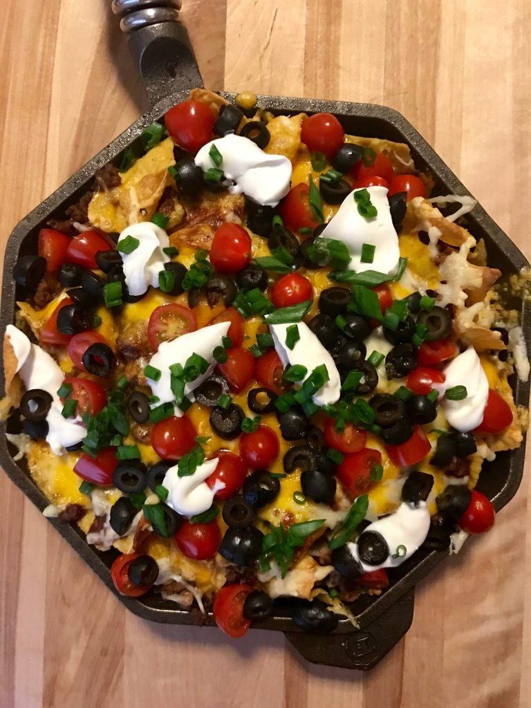 Skillet nachos topped with chili, tomatoes, olive, sour cream, cheese, and cilantro.