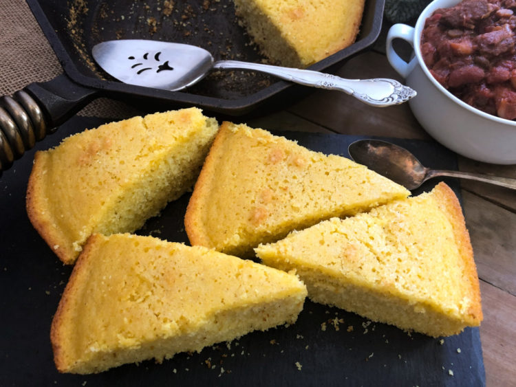 Triangle slices of sweet cornbread on a black platter.