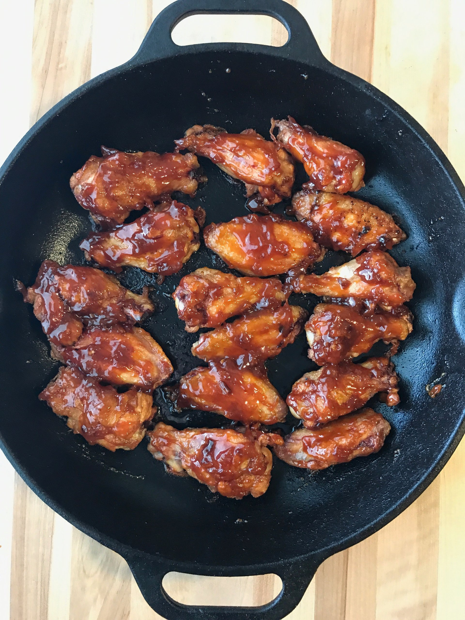 Top view of Smoked Maple-Bourbon Chicken Wings in a cast iron pan