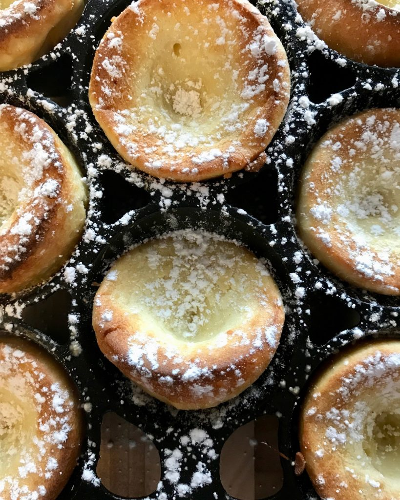 Popovers in cast iron bakeware sprinkled with powdered sugar.
