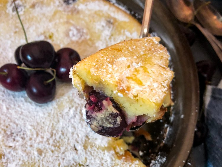 A serving or bite of cherry clafoutis right from the skillet.