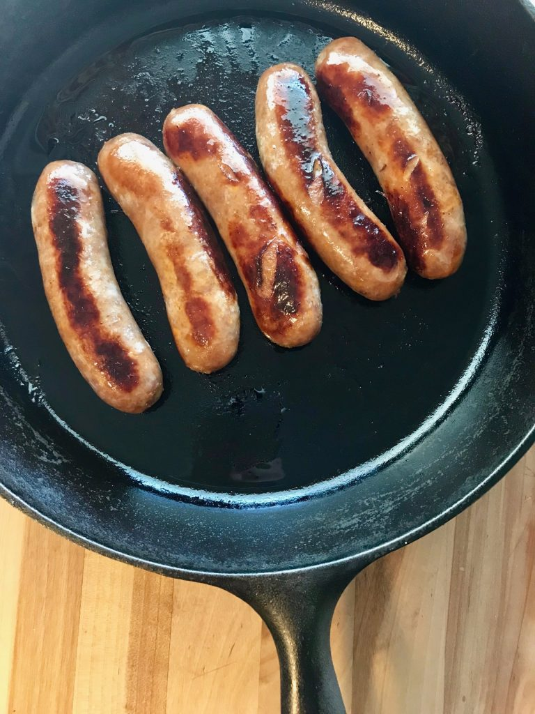 Five seared bratwursts stuffed with bacon and cheese in a cast iron skillet.