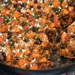 Cast iron skillet of chicken, sweet potatoes, black beans, and tomatoes with Mexican seasonings, garnished with cilantro and queso fresco.