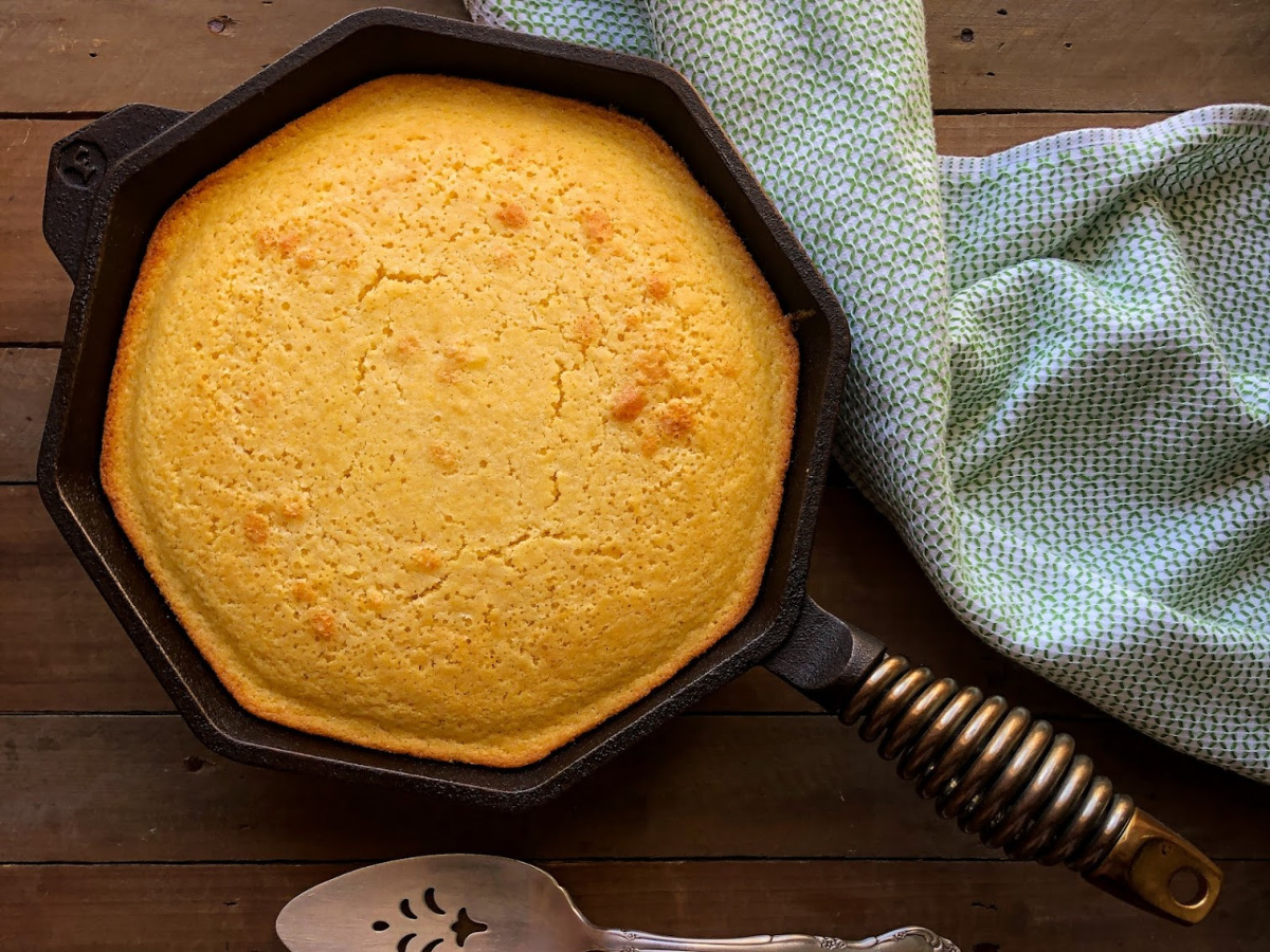 Cast Iron Sweet Cornbread freshly baked in a skillet with a towel and slice server.
