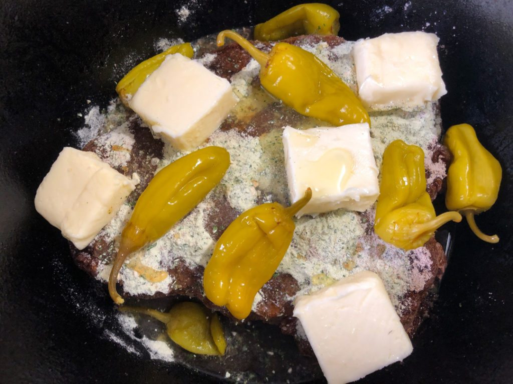 Cubed butter, peperoncini peppers with 1/4 cup of their liquid have been added to the roast in the Dutch oven.