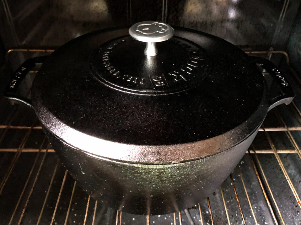 The lid has been placed on the Dutch oven and the roast has been put in the oven.