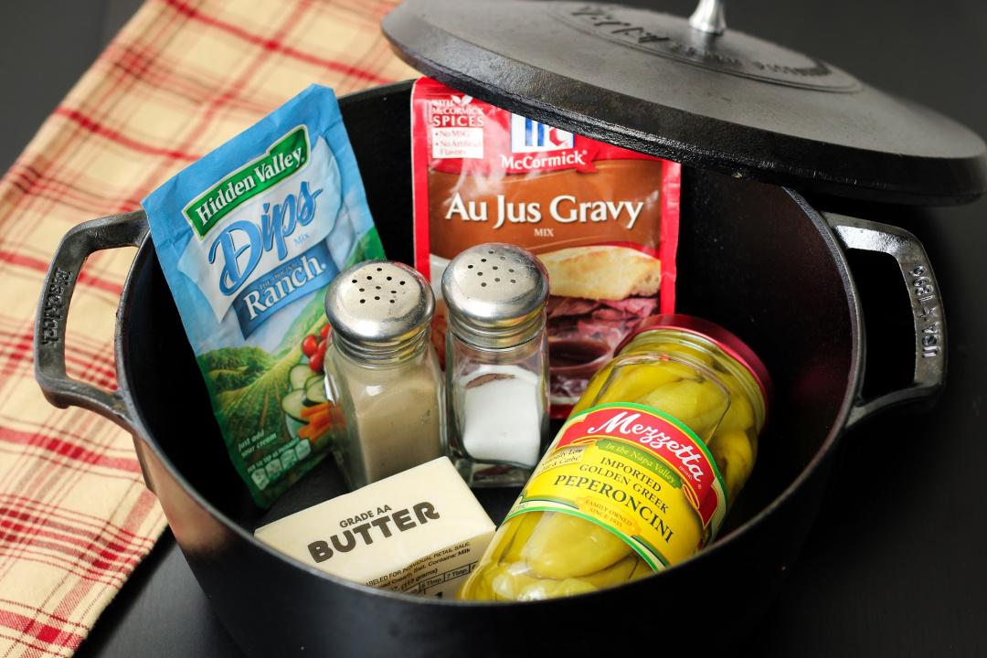 Au jus mix, Ranch mix, butter, pepperoncinis, salt and pepper inside a Dutch oven.