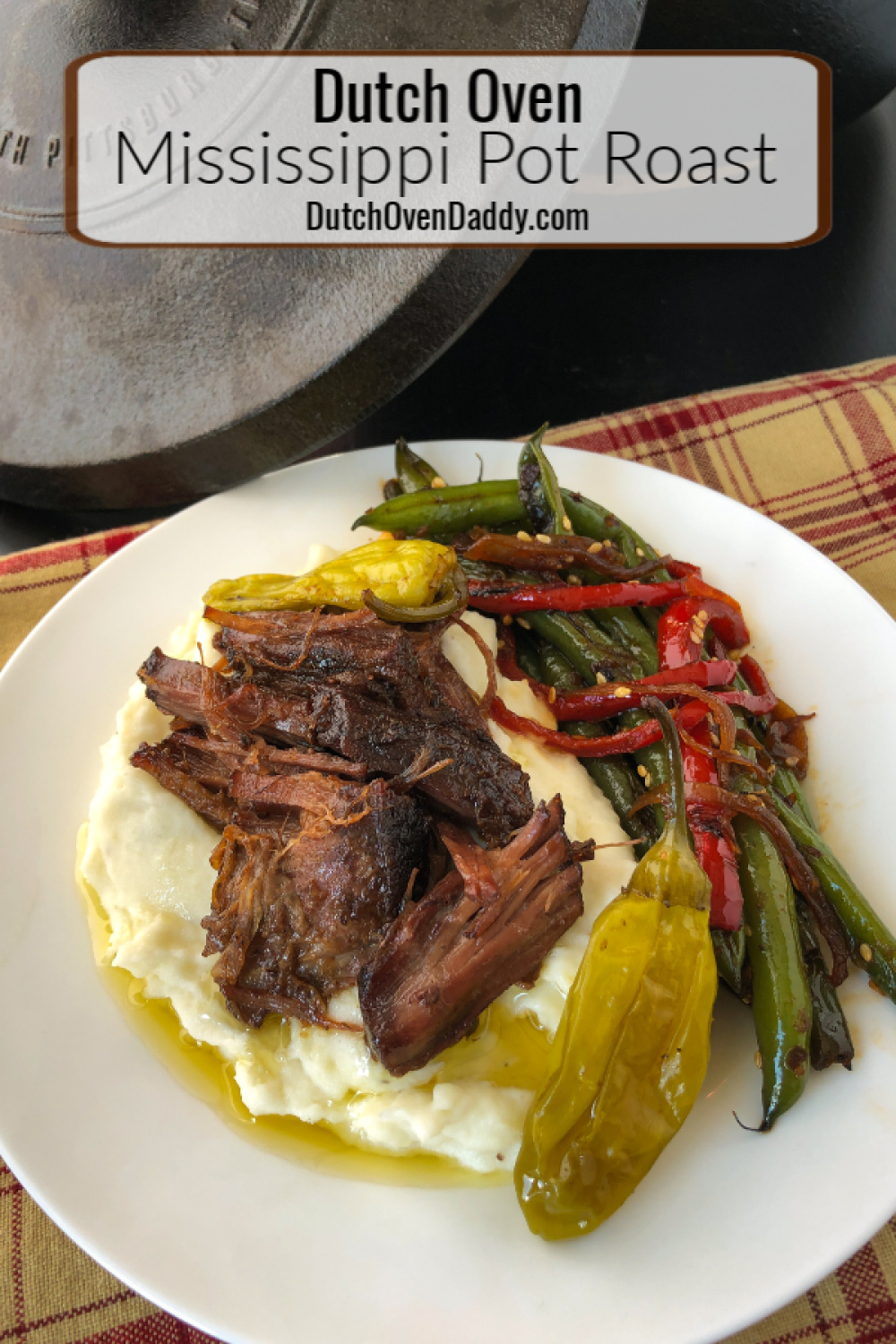 Plated pot roast over mashed potatoes with a side of green beans. Dutch oven in the back ground.