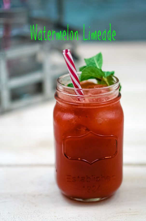 Fresh watermelon limeade in a mason jar glass with a red and white straw and garnish of fresh mint.