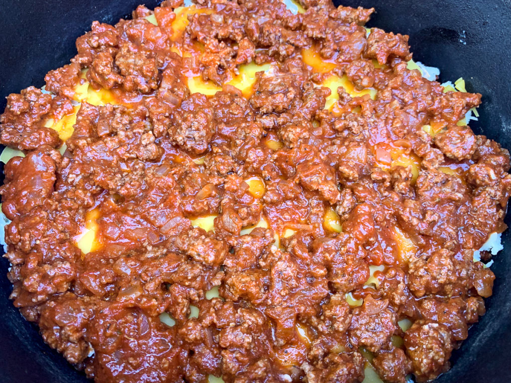 The final portion of meat sauce has been layered over the top layer of dried lasagna.