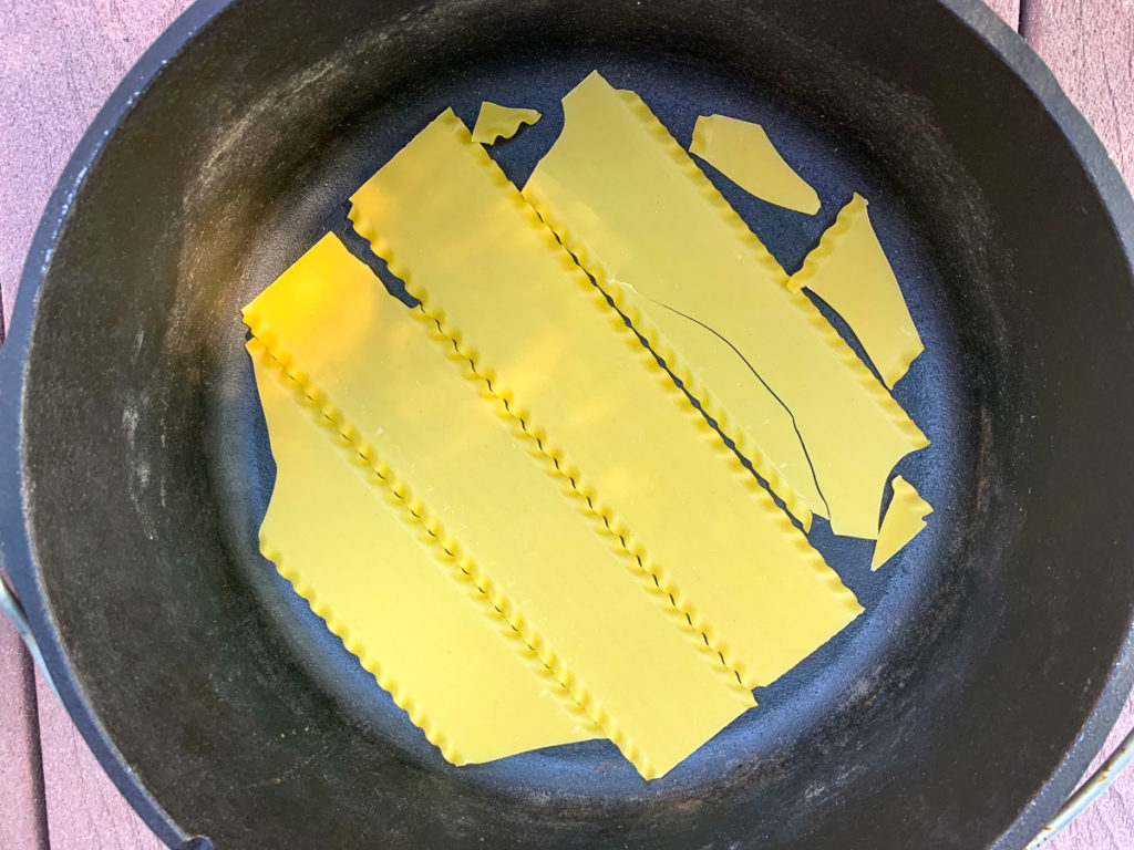 Dried/uncooked lasagna noodles have been placed in the bottom of the camp oven, some are broken to fit the roundness of the vessel.