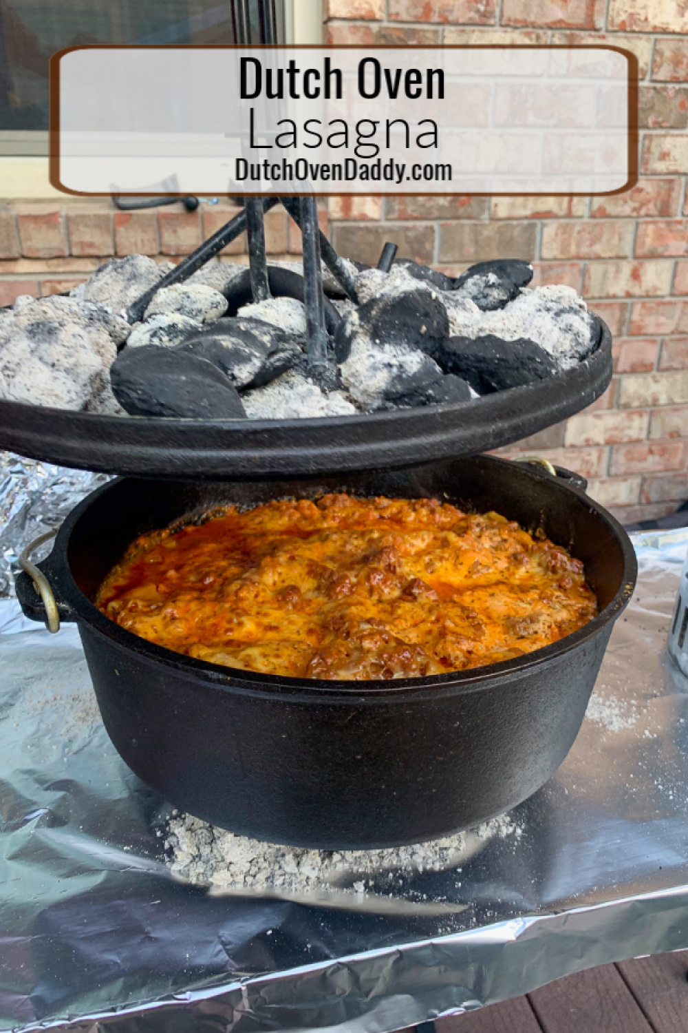 The lid being raised off the camp oven with the charcoal on top revealing the cooked lasagna.