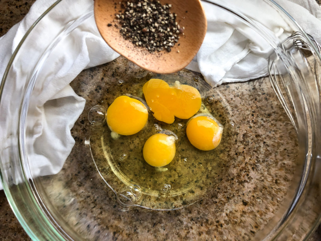 Freshly cracked black pepper being added to a bowl with four large eggs.