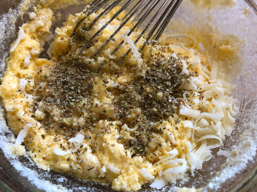 Parmesan and mozzarella cheeses and oregano have been added to four beaten eggs and will be whisked together.