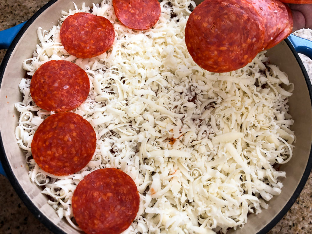 Sliced pepperoni is being added to on top of the shredded mozzarella.