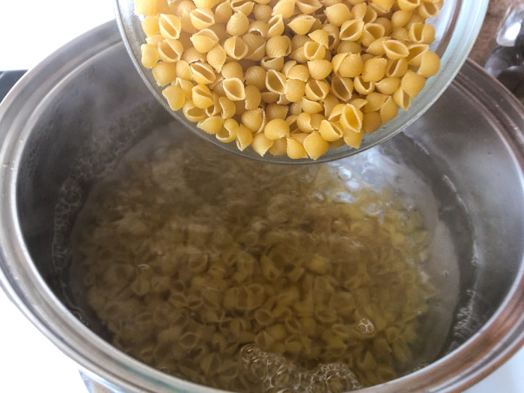Small shell pasta being added to boiling water.