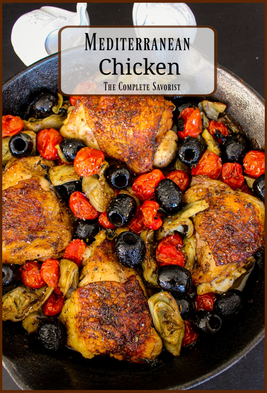 Balsamic glazed chicken thighs, olives, artichokes, and tomatoes in a cast iron skillet