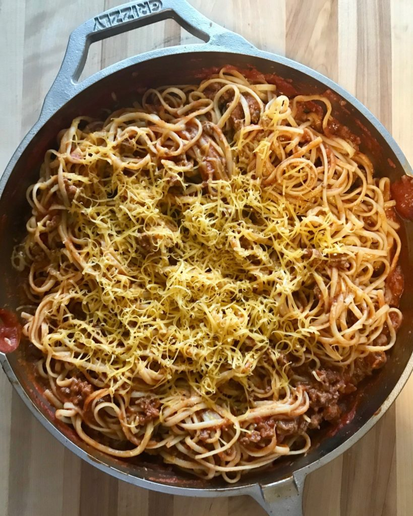 Cast Iron Skillet full of Taco flavored spaghetti topped with cheddar cheese.
