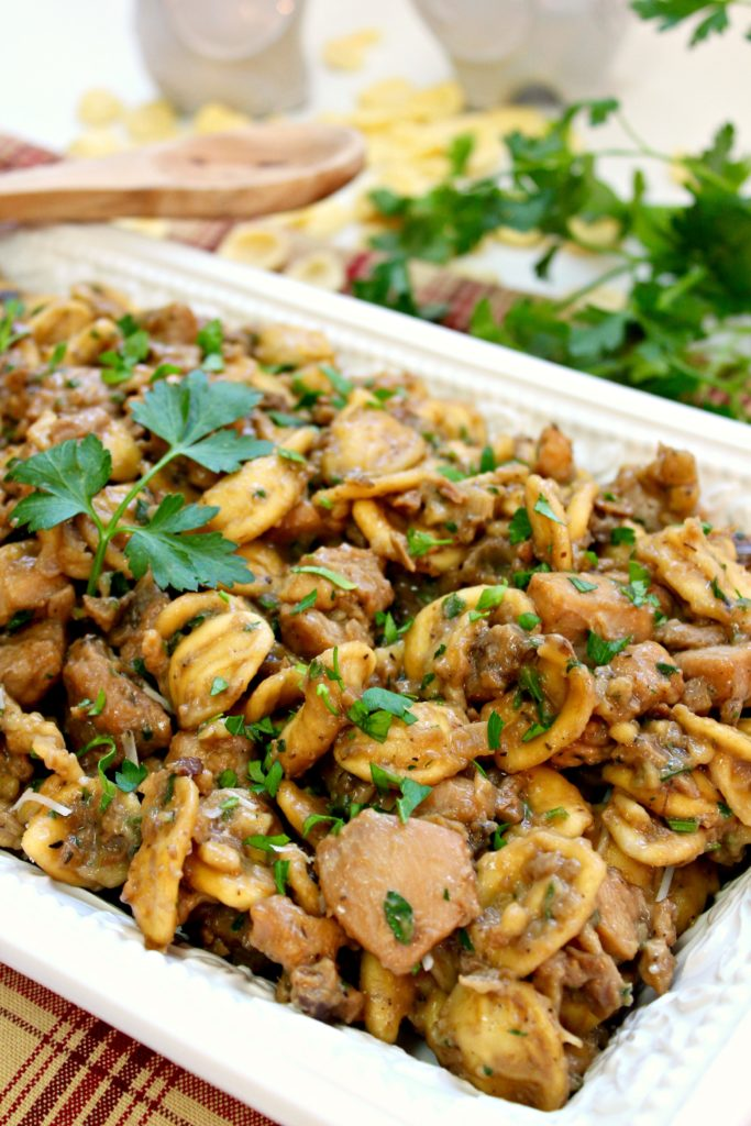 A serving platter of chicken and orecchiette pasta tossed in a mushroom sauce and garnished with fresh parsley.