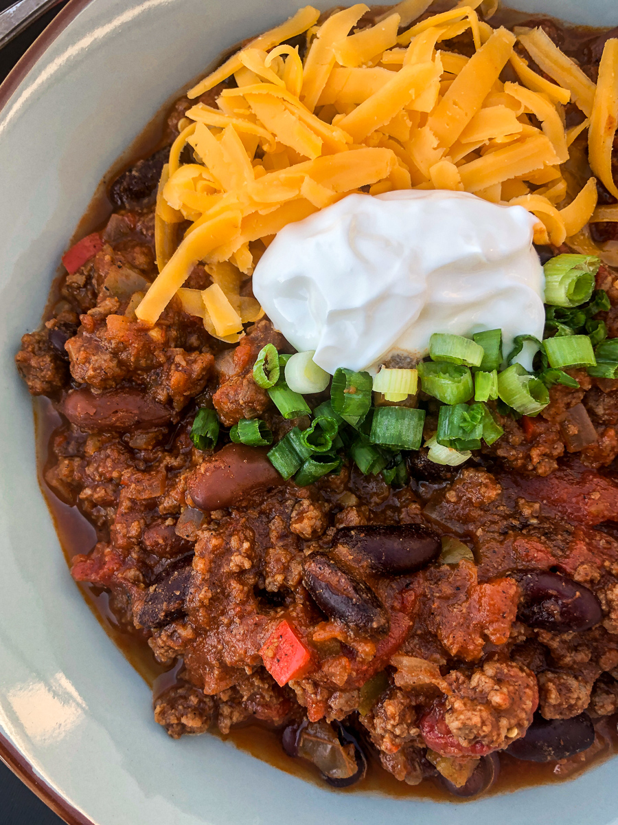 Close up and side view of Awesome Chili in a blue-gray bowl garnished with sour cream, green onions, and shredded cheddar cheese.