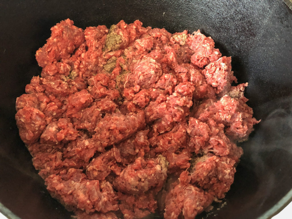 Lean ground beef crumbled into a hot dutch oven.