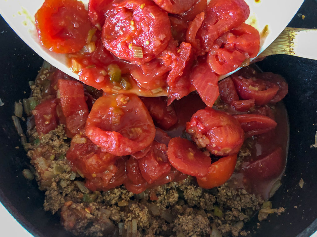 The salsa and tomatoes are being added to the chili base in the dutch oven.