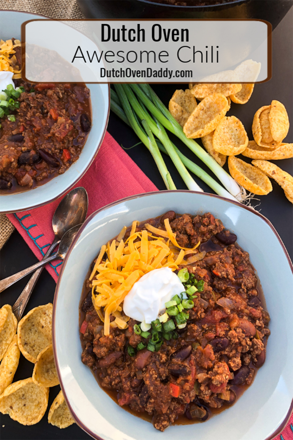 Awesome Chili served up in bowls topped with sour cream, cheddar cheese, and green onions, Frito chips sprinkled around.