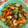 Dutch Oven Honey Glazed Carrots in a green serving bowl garnished with fresh thyme.