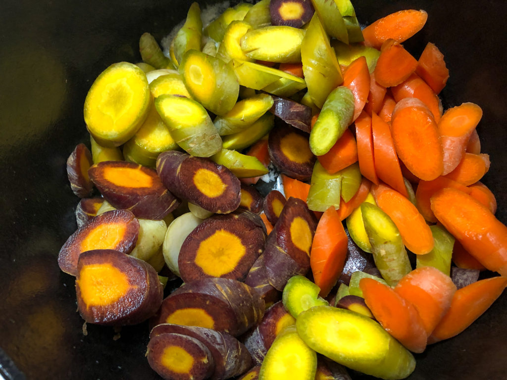 White, yellow, orange, and purple diagonally sliced carrots are added to the melted butter in the Dutch oven.