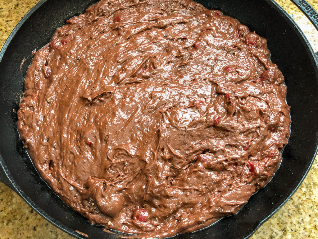 Chocolate cherry cake batter has been poured and smoothed into the prepared cast iron skillet.