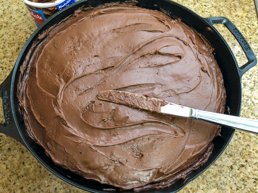 The freshly baked chocolate cherry cake has been frosted while still in the skillet with a butter knife in view.