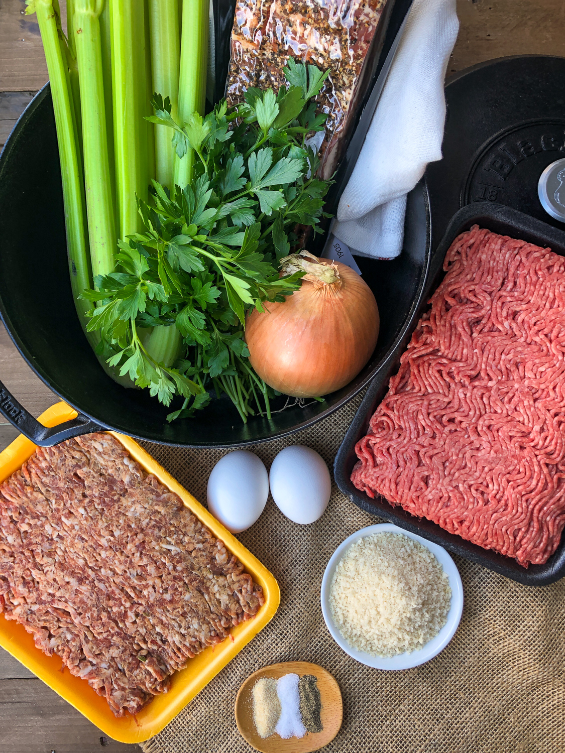 Ingredients to make the meatloaf: ground Italian sausage, ground beef, eggs, panko, onion, celery, peppered bacon, fresh parsley, seasonings, and a dutch oven.
