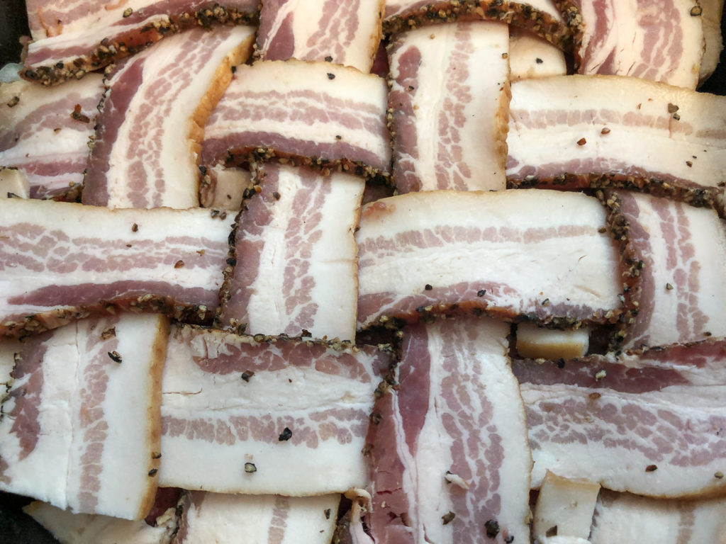 Peppered bacon has been applied to the top of the meatloaf in a lattice weave.