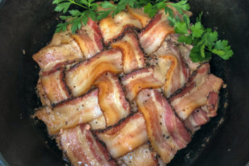 Cooked Dutch oven peppered bacon meatloaf garnished with fresh parsley