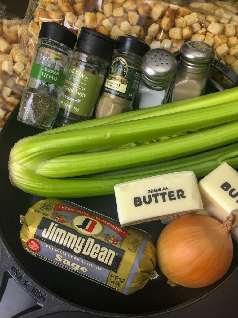 Ingredients needed to make the dressing: Sage Pork Sausage, onion, butter, celery, dried bread, herbs, and seasonings, all nestled in a cast iron skillet.