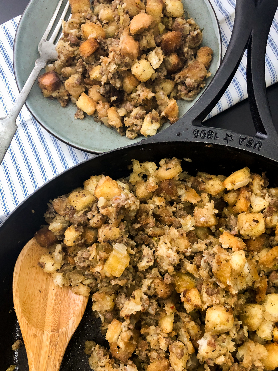 Cooked and served sausage stuffing portioned onto a blue plate with a fork and the rest remaining dressing in the skillet with a wooden spoon.