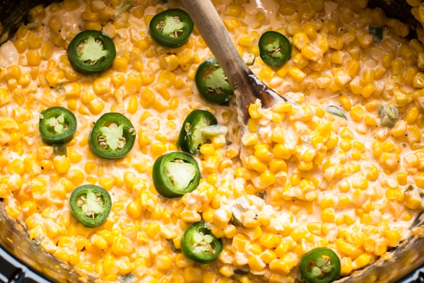 Slow cooker crock full of cheesy creamy corn with slices for fresh jalapeño.