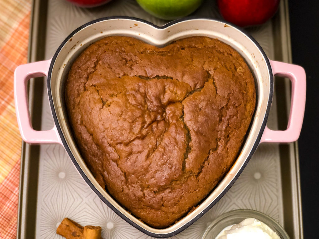 Freshly baked apple cake in a pin heart shaped enameled dutch oven.