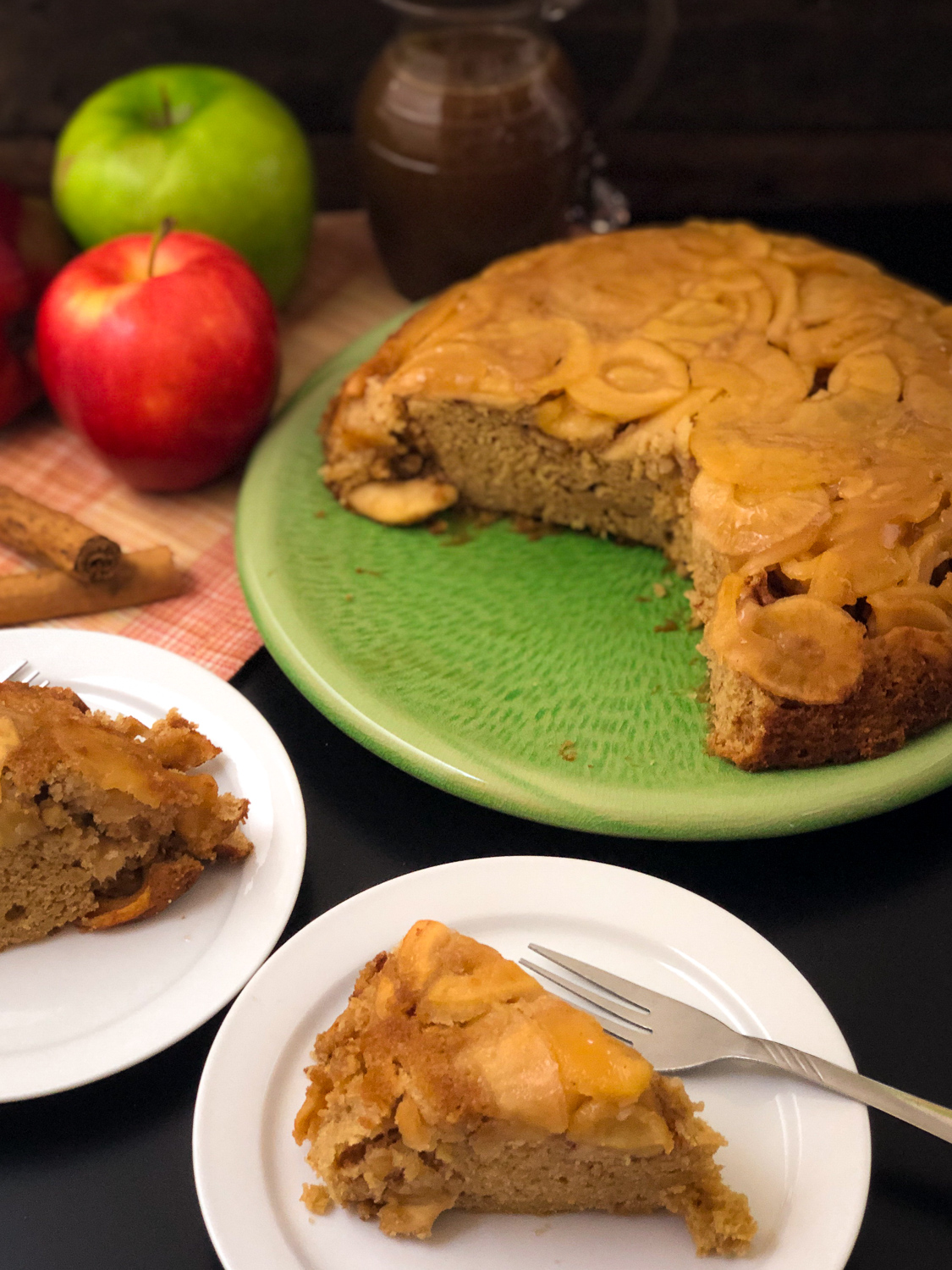 Two slices of apple cake with the remaining on a platter in the background.