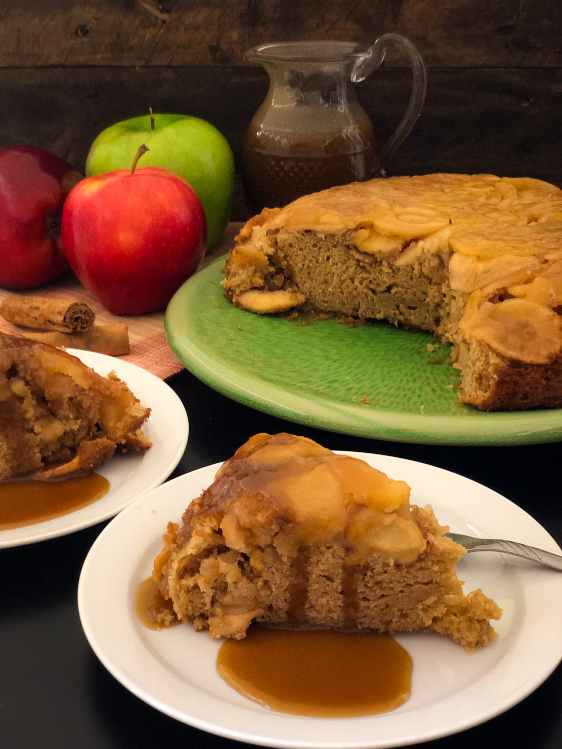 Slices of Dutch oven apple cake on white plates with caramel sauce poured over; remaining cake on green platter with pitcher of caramel sauce in the background.