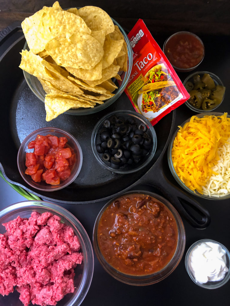 Ingredients needed for making skillet nachos: green onions, tortilla chips, tomatoes, olives, jalapeños, taco seasoning, cheeses, salsa, chili, ground beef, and sour cream.
