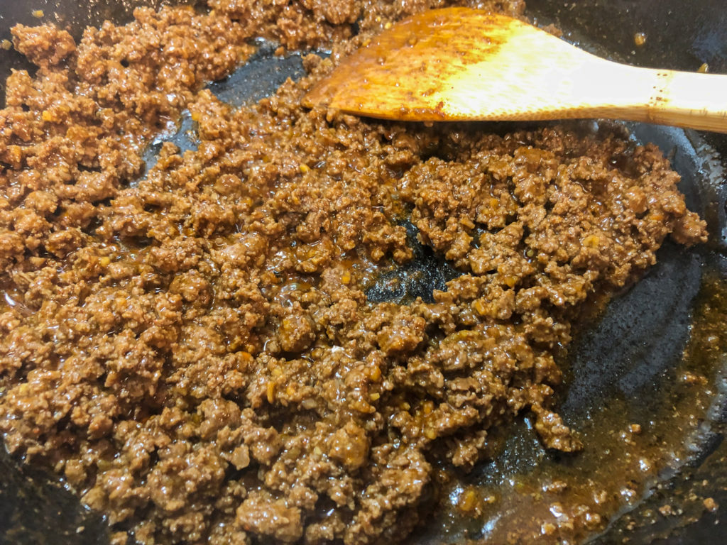 Browned ground beef in a cast iron skillet with taco seasoning added.