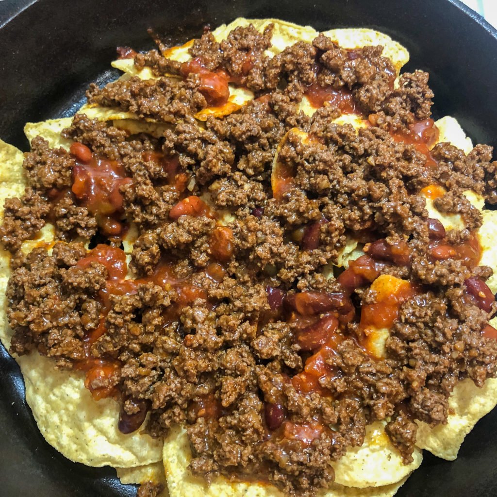 Corn tortilla chips layered in a cast iron skillet topped with canned chili and taco meat.