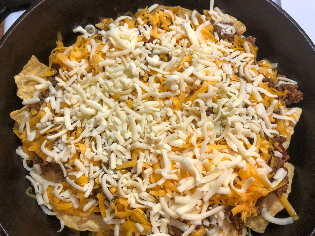 Cheddar and Monterey Jack cheeses over the chili and meat.