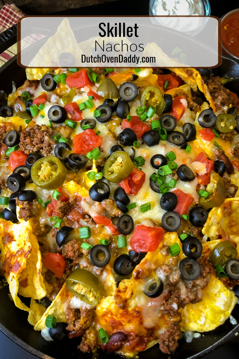 Skillet full of loaded nachos with sour cream and salsa in the background.