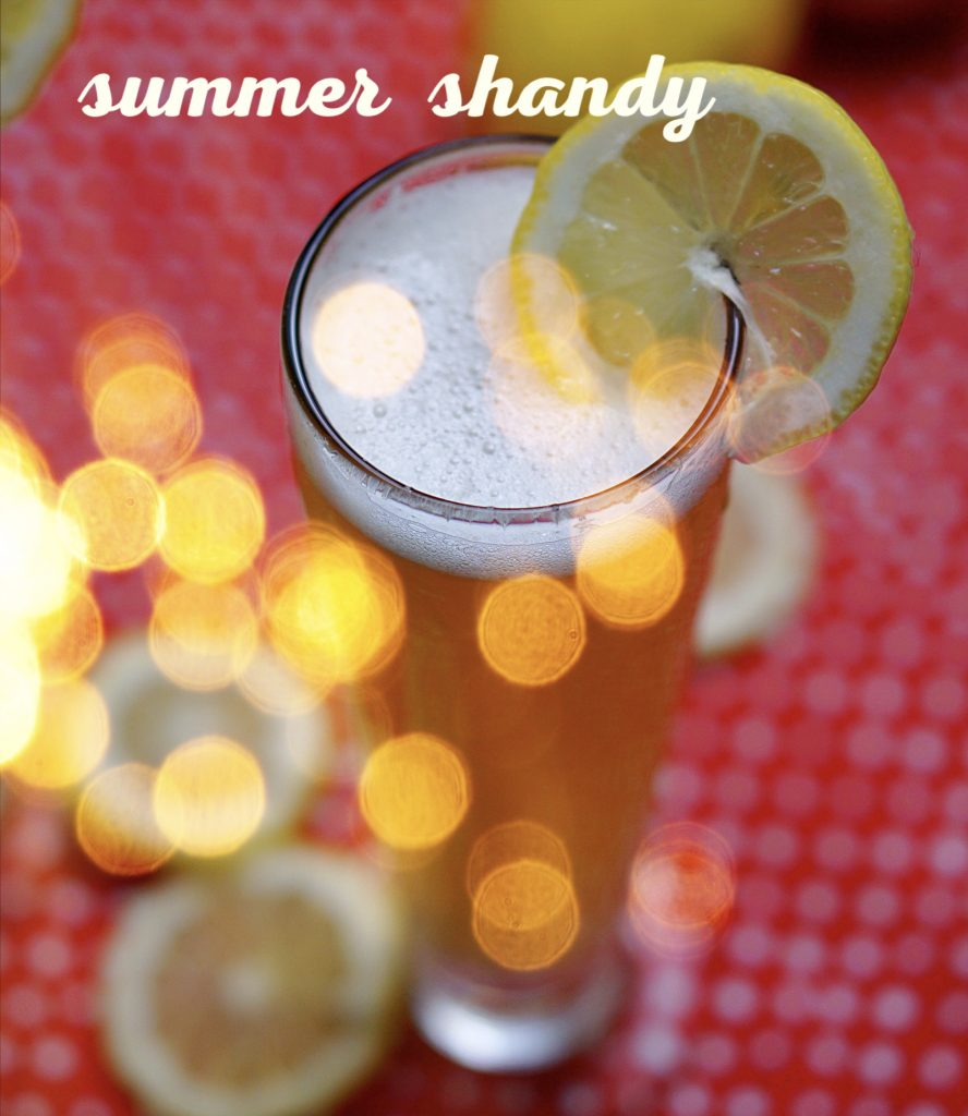 Artsy image of pilsner glass with Summer Shandy, garnished with a lemon wedge from Wet Whistle Drinks.