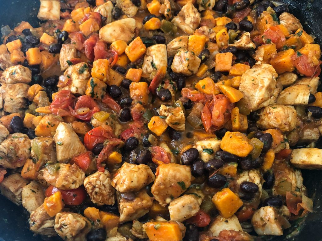 Sweet potatoes, black beans, and cheese have been added to the skillet, completing the dish.