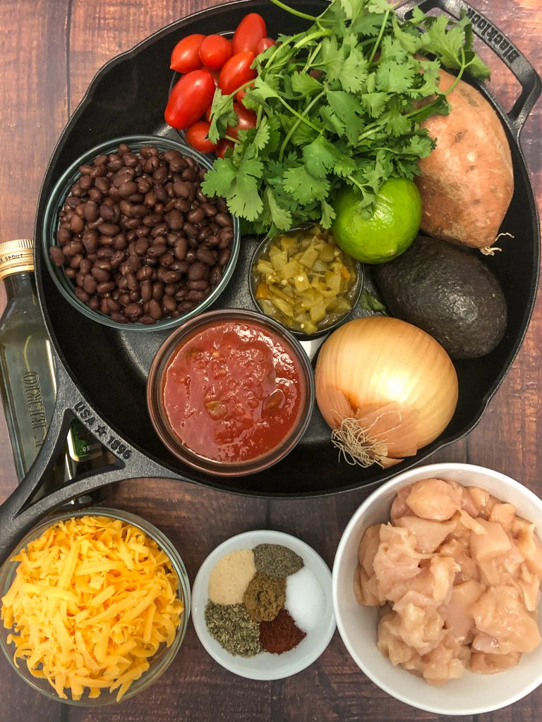 Ingredients to make the meal: black beans, grape tomatoes, cilantro, sweet potato, lime, green chilies, avocado, onion, salsa inside a cast iron skillet; olive oil, cheese, spices, and chicken.